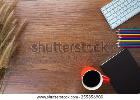 notebook, pencil, grass on wooden table and cup of coffee on wooden table