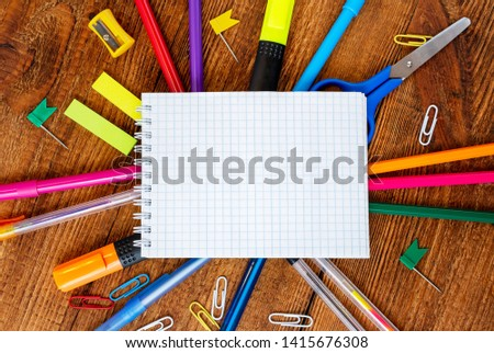 Notebook sketchbook blank page with colorful pencils, markers and pen composition mock-up Back to school concept with stationery office supplies on a blue wooden background with copy space top view