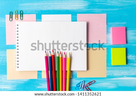 Notebook sketchbook blank pages with colorful pencils, markers and pens composition mock-up Back to school concept with stationery office supplies on a blue wooden background with copy space close-up