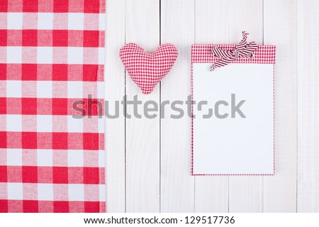 Notebook, tablecloth, heart on white wood table