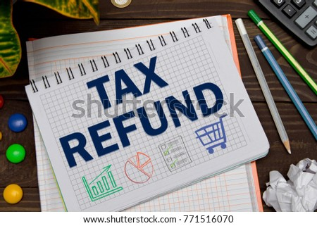 Notebook with a Business notes TAX REFUND on the office table with tools. Concept TAX REFUND with elements of infographics