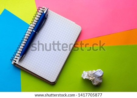 Notebook with blue pen and crumpled sheets on the background of colored sheets of paper