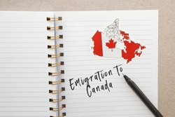 notebook with canadian flag and country map with inscription emigration to Canada, emigration concept