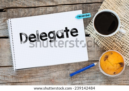 Notebook with delegate sign. Notebook with delegate sign and sticker remember on wooden desk with cup of coffee and muffin