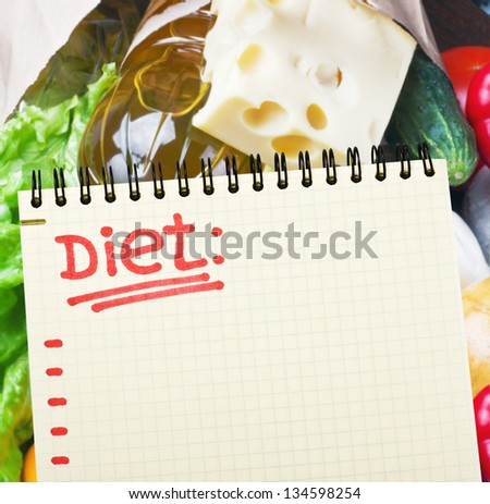 notebook with diet plan against food supermarket