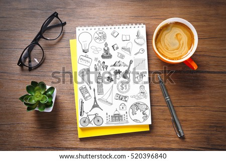 Notebook with drawings and cup of coffee on wooden table. Creative concept.