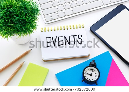 Notebook with events word on computer desk with pencil notepad and clock for event planning concept #702572800