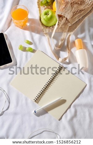 Notebook with fruit, sun cream, bag on white fabric background.