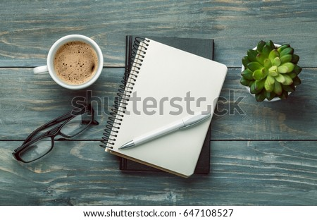 Notebook with glasses and coffee.