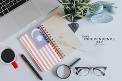Notebook with Malaysia Flag on white office table with text Happy Independence day 31st August.