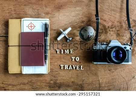 Notebook with map passport and camera on wooden background with word Time to travel