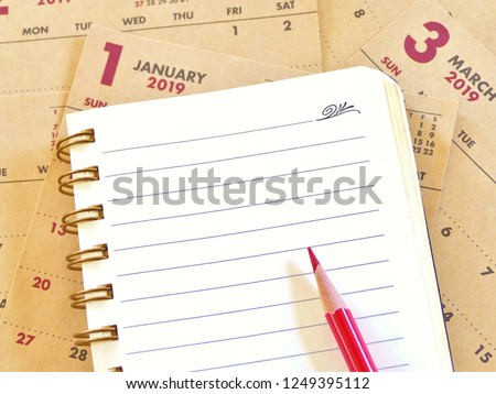 notebook with message and red pencil to t o write resolutions list / goal / plan  for nex year plan with a 2019 calendar as a background