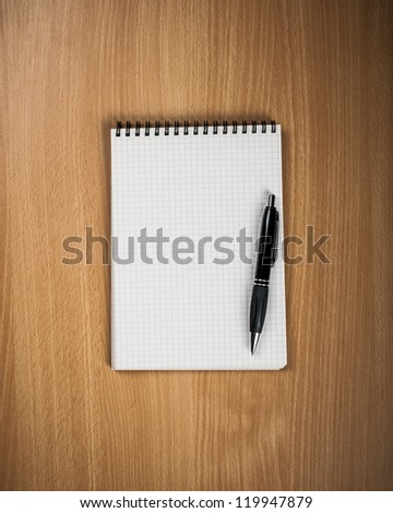 Notebook with pen on wood background - Back to school concept