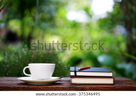 Notebook with pencil and cup on wooden table