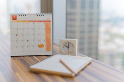 Notebook with pencil diary clock on table with October 2019 calendar at office work place with blurred background. Planning scheduling agenda Event organizer writing detail. Calendar concept.