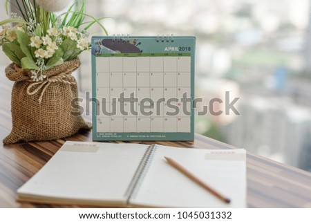Notebook with pencil diary on table with April 2018 calendar at office work place. Blurred Background, Planning scheduling agenda, Event, organizer writing detail of plan for 2018. Calendar concept. #1045031332