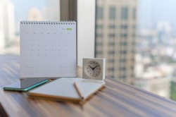 Notebook with pencil diary smartphone clock on table with May 2020 calendar at office work place with blurred background. Planning scheduling agenda Event organizer writing detail. Calendar concept.