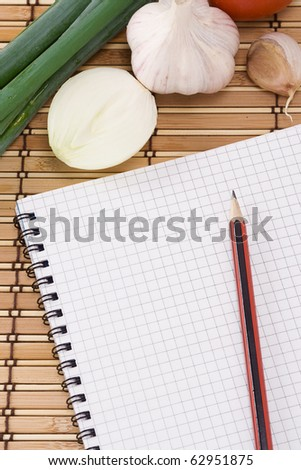 notebook with pencil, garlic, tomato and onion on straw texture