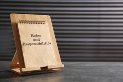 Notebook with phase Roles and Responsibilities on grey stone table, space for text
