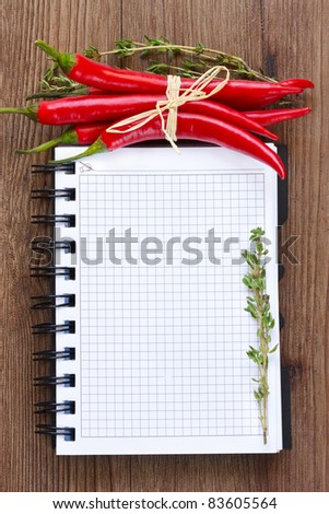 Notebook with red chili and thyme on a wooden board.