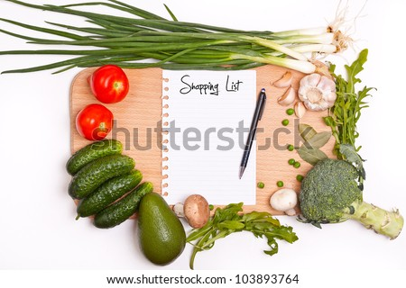 Notebook with shopping list in the cutting board - stock photo