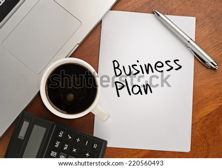 Notebook with text Business Plan on table with coffee, calculator and notebook