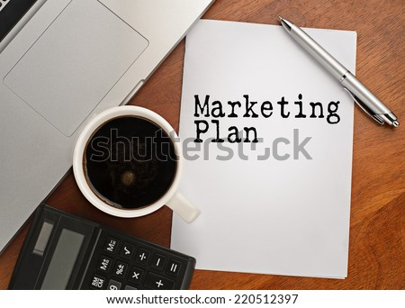Notebook with text marketing plan on table with coffee, calculator and notebook