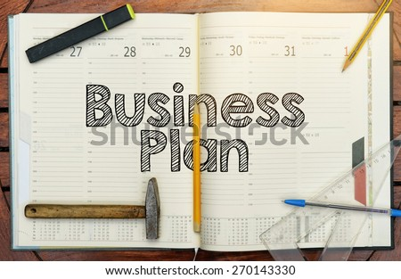 notebook with the note in the center about the Business Plan