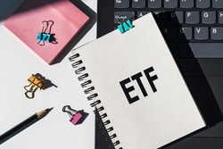 Notebook with tools and notes about ETF (Exchange Traded Fund) lies on laptop.