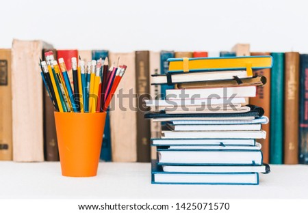 Notebooks piles, stack of books education back to school background, textbooks and pencils in plastic holder with copy space for text