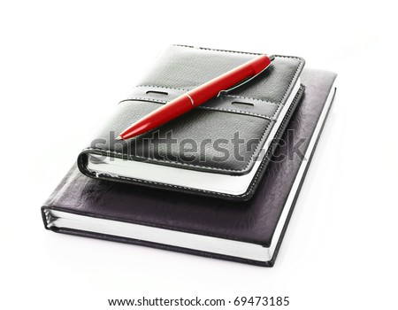 Notebooks with a blue ballpoint pen on them isolated on white