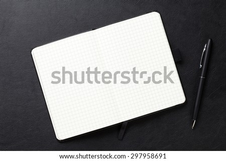 Notepad and pen on office leather desk. Top view with copy space