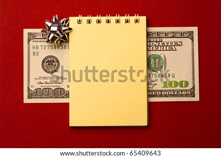 Notepad, dollar and bow isolated on red