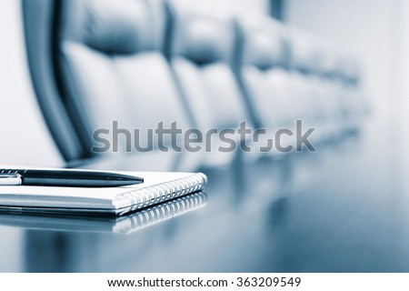 Notepad for agenda kept on table in empty corporate conference room before business meeting in blue tone