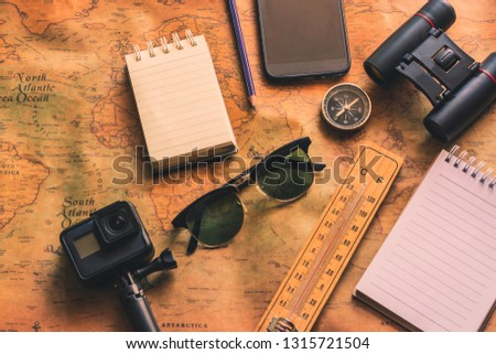Notepad for note with binoculars pencil, compass on paper map for travel adventure discovery image