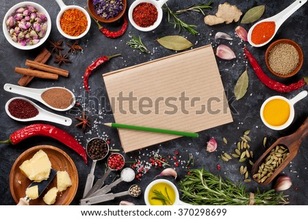 Notepad for your recipe with herbs and spices over black stone background. Top view with copy space
