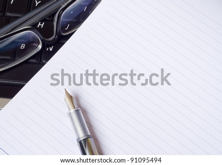 notepad, glasses and a pen on top of a laptop