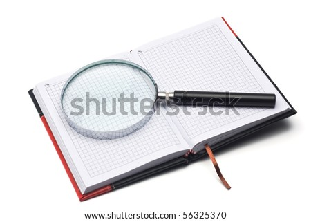 notepad in the red-black cover and hand magnifier