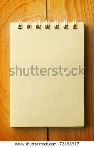 Notepad isolated on wooden background