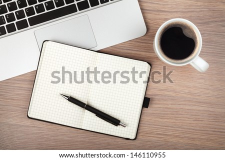 Notepad, laptop and coffee cup on wood table. View from above