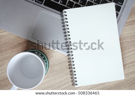 notepad on the laptop and cup on office wooden table #508336465