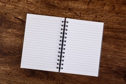 Notepad on the wooden rustic desk. Mockup design concept with empty notebook page. Mock-up of blank diary. Wooden rustic desk.