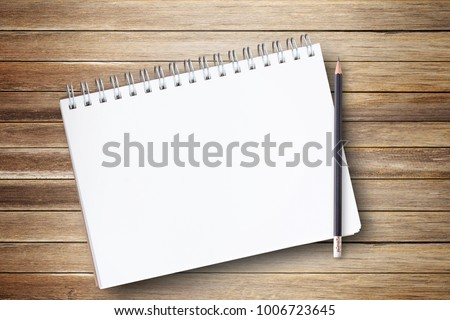 Notepad or notebook with pencil on brown wood table background.using wallpaper for education, business photo.Take note of the product for book with paper and concept, object or copy space. #1006723645