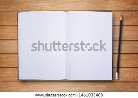 Notepad or notebook with pencil on brown wood table background.using wallpaper for education, business photo.Take note of the product for book with paper and concept, object or copy space. #1461033488
