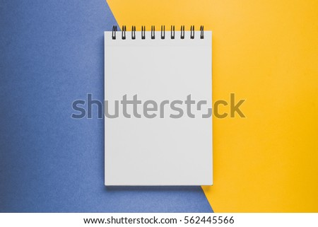 Notepad or sketchbook  on the yellow-blue background. Creativity concept