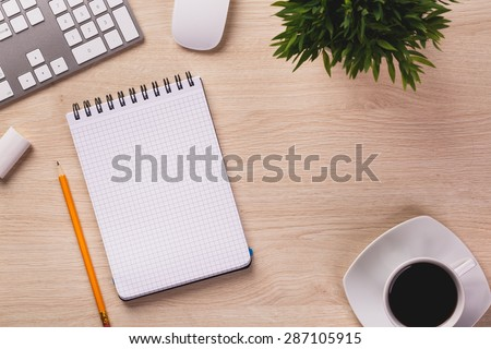 Notepad, pencil, white computer keyboard, mouse, plant and cup of coffee on wooden office desk.