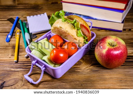 Notepad, pens, ripe apple, stack of books and lunch box with hamburger, cucumbers and tomatoes on rustic wooden table