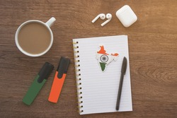 notepad with india flag, wireless headphones, coffee cup, pen, markers on brown table, study concept