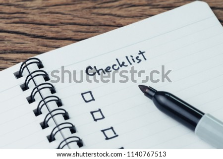 Notepad with pen and handwriting headline as Checklist with check box on wood table, to do list, prioritize or reminder for project or plan.