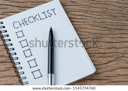 Notepad with pen and handwriting headline as Checklist with check box on wood table, to do list, tasks prioritize or finish or not yet reminder for project or plan.